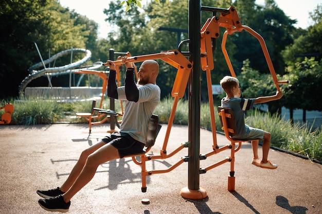 エクササイズマシンでの父と子、屋外の遊び場でのスポーツトレーニング。家族は夏の公園で健康的なライフスタイル、フィットネストレーニングをリードしています