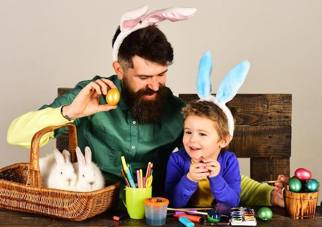 父と子はイースターエッグを描いています。塗られた卵が付いているバスケットを保持しているイースター家族。