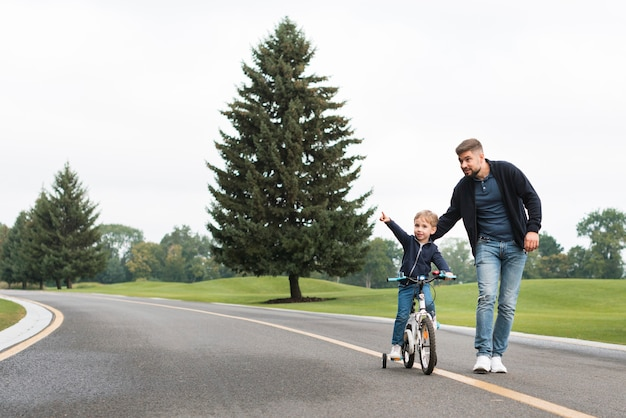Отец и ребенок играют в парке с велосипедом