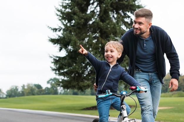 Отец и ребенок, играя в парке