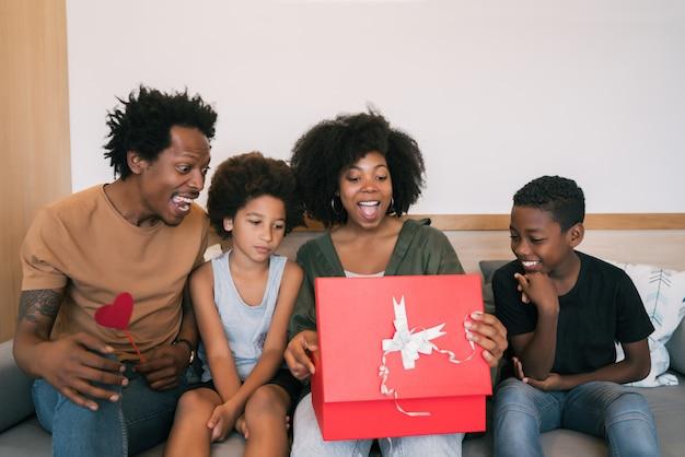Отец и дети поздравляют маму с днем матери.