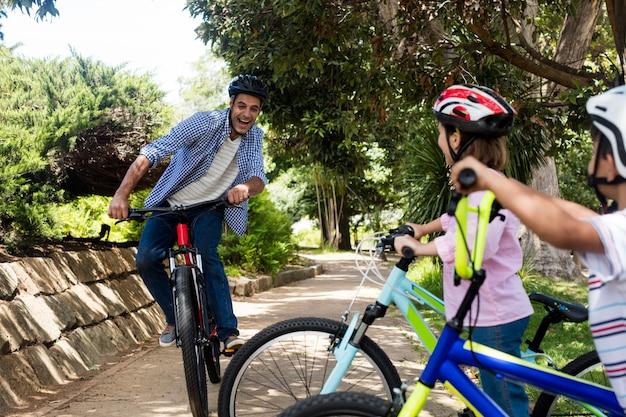 Отец и дети на велосипеде в парке