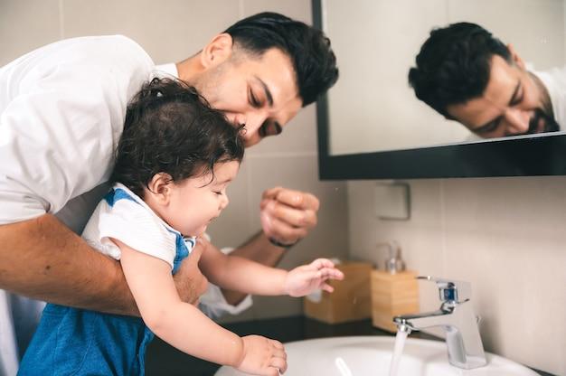父と子供たちは家で一緒に幸せ、男は若い幼児の息子と笑顔で楽しんでいる子供時代の家族と一緒にかわいい赤ちゃん、小さな娘や男の子のライフスタイルを愛し、気遣う