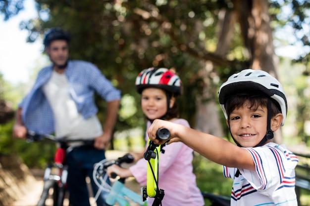 아버지와 어린이 공원에서 자전거와 함께 서
