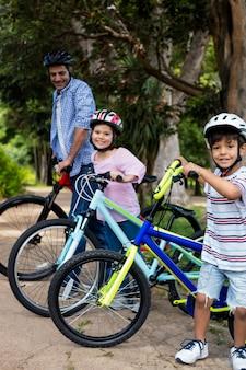 父と子供たちは公園で自転車で立っています。