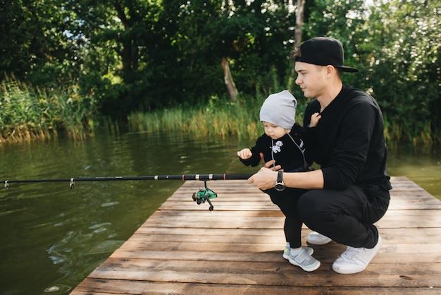 父とかわいい1歳の息子が自然の中で釣り竿を使って釣りをしています。田舎の休暇の概念。釣りの日に関する記事。