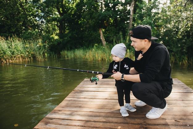 父とかわいい1歳の息子が自然の中で釣竿で釣り。田舎の休暇の概念。釣りの日に関する記事。