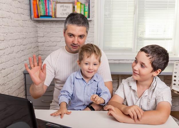 Отец и милые сыновья делают видеозвонок с семьей на цифровом планшете