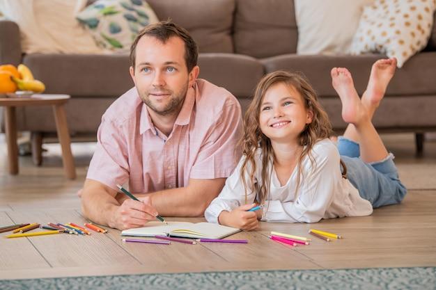 Отец и дочь рисуют вместе, лежа на полу в комнате квартиры.