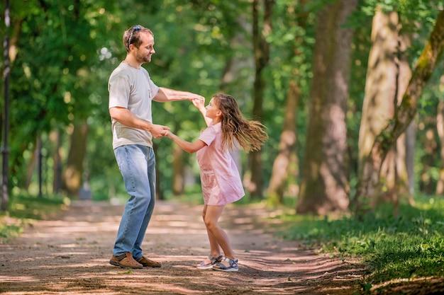 아버지와 딸이 공원에서 춤을 추고 있습니다. 행복한 가족 개념입니다. 가족 야외 라이프 스타일과 아름다움 자연 장면입니다. 함께 쉬고 있는 행복한 가족. 가족 생활의 행복과 조화.
