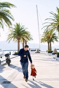 父と娘は海沿いのヤシの木の隣で手をつないで走っています。