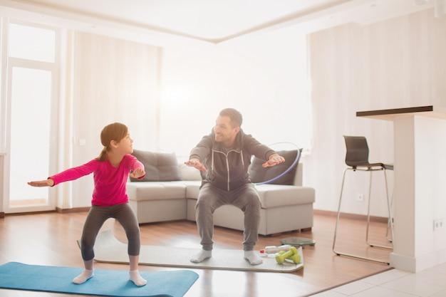 父と娘は自宅でトレーニングしています。アパートでのエクササイズ。スクワットエクササイズを自宅で行う。かわいい子供とパパは彼女の部屋の窓の近くの屋内マットでトレーニングしています