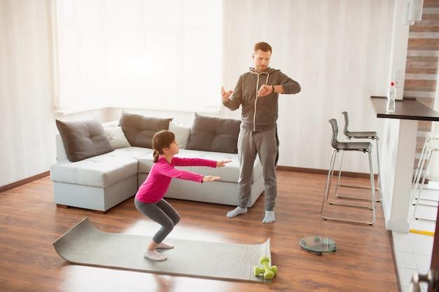 父と娘は自宅でトレーニングしています。アパートでのエクササイズ。自宅でのスポーツ。パパはスポーツウォッチを使用し、娘はスクワットエクササイズをしています