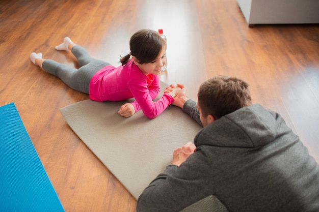 Отец и дочь тренируются дома. тренировки в квартире.