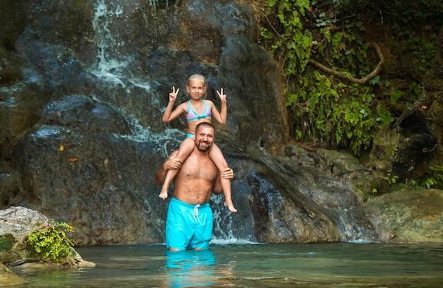 Отец и дочь у водопада в джунглях. путешествие на природе возле красивого водопада, турция.