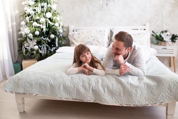 ベッドの上のクリスマスツリーの近くに家で父と娘
