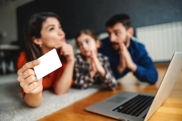父と娘が母親にインターネットでいくつかの商品を買うように懇願する。クレジットカードを持って、お金を使うかどうか考えている母親。クレジットカードで手に選択的な焦点。