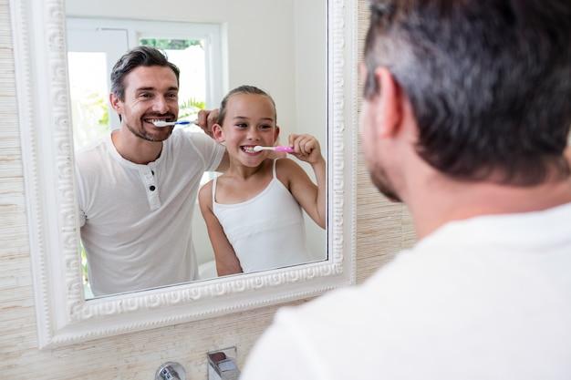 Отец и дочь чистят зубы в ванной комнате