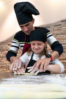 아버지와 딸이 함께 요리사의 의상을 입고 과자를 요리