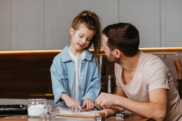 家の台所で料理をしている父と娘