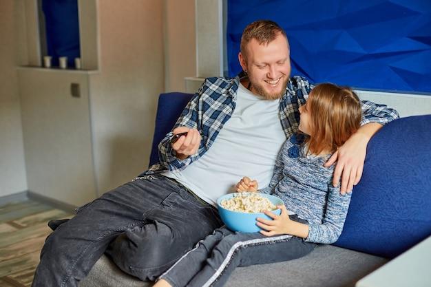 父と娘はポップコーンを食べてテレビ映画を見る、父と子の女の子は自宅のソファで映画を見る