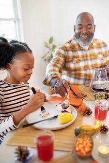 추수 감사절 저녁 식사를 즐기는 아버지와 딸