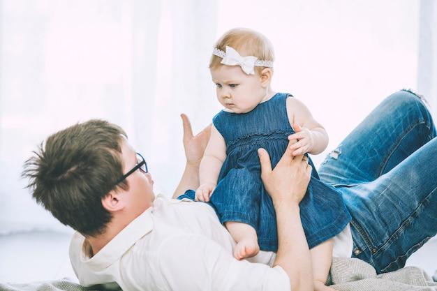 Семья отца и дочери счастлива вместе дома улыбается