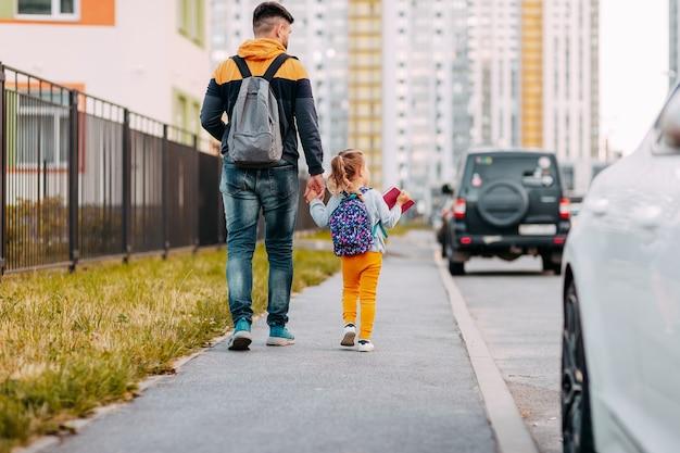 Отец и дочь впервые идут в школу. снова в школу после пандемии.