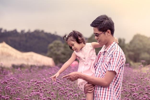 Отец и дочь веселятся в цветнике