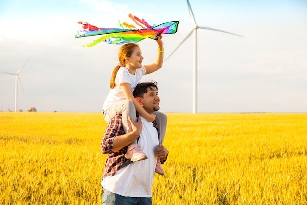 Отец и дочь веселятся, вместе играют с воздушным змеем на пшеничном поле в яркий летний день