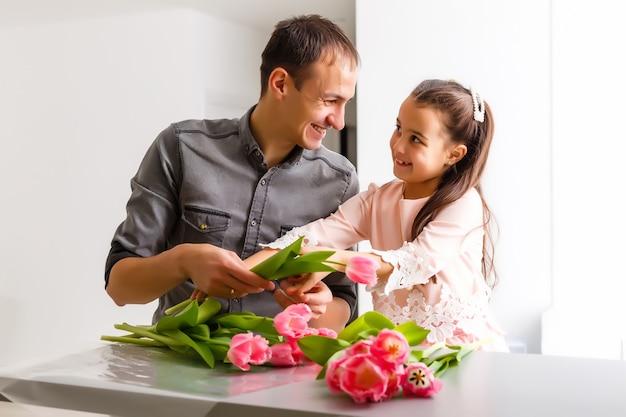 Отец и дочь, держа букет тюльпанов
