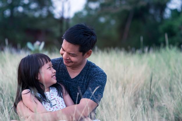 사랑으로 녹색 자연에서 포옹하는 아버지와 딸