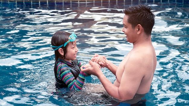 Отец и дочь обнимаются в бассейне