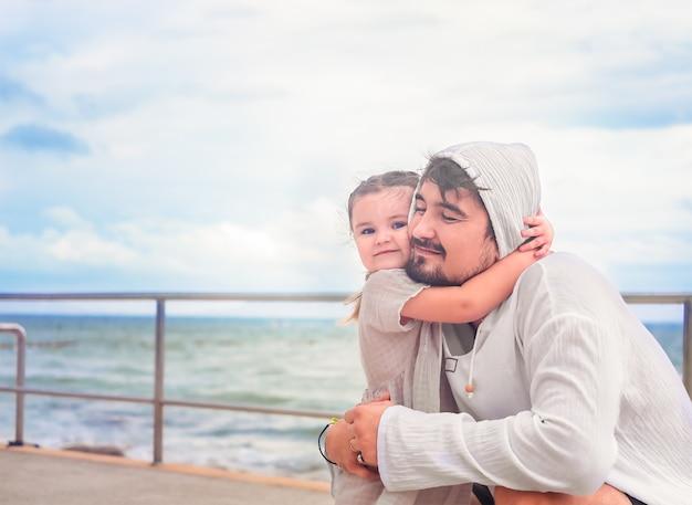 아버지와 딸이 바다 전망과 함께 산책에 포옹 프리미엄 사진