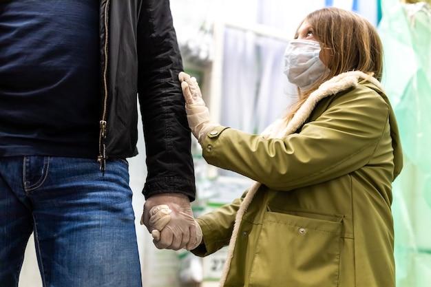 Отец и дочь в строительном магазине в медицинских защитных масках и одноразовых перчатках