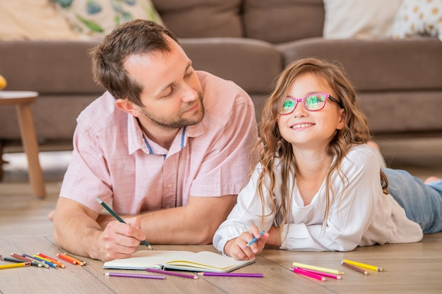 Отец и дочь в очках рисуют вместе, лежа на полу в комнате квартиры.