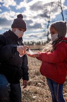 손, 개인 위생에 알코올 안티 박테리아 스프레이를 적용하는 마스크의 아버지와 딸