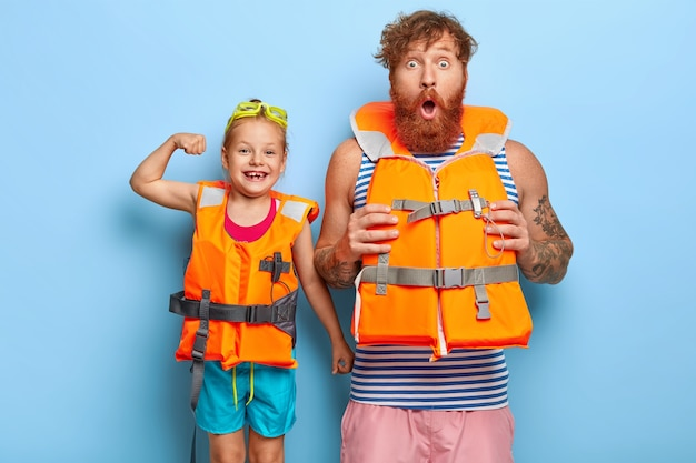 Отец и дочь в спасательных жилетах собираются заняться экстремальной активностью на воде. шокированный бородатый рыжий мужчина смотрит в камеру
