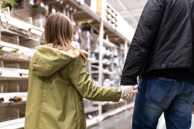 Отец и дочь в магазине в одноразовых перчатках
