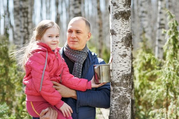 Отец и дочь в лесу с кружкой для сбора урожая