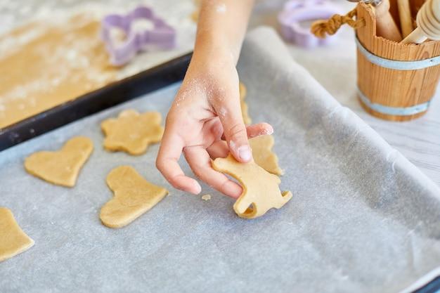 父と娘がカビでクッキーを作り、キッチンで一緒に、家庭での家族の料理、幸せな家族のライフスタイル。