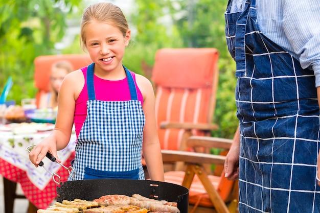 소시지와 고기와 함께 여름에 정원에서 바베큐를 만드는 아버지와 딸