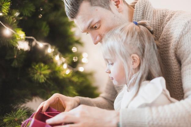 父と娘、照明付きクリスマスツリーの隣