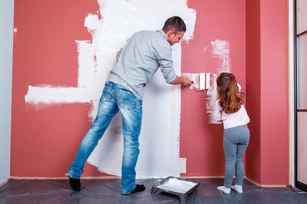Отец и дочь красят стену в комнате. ремонт дома