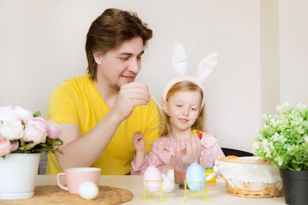 イースターのために卵を描く父と娘