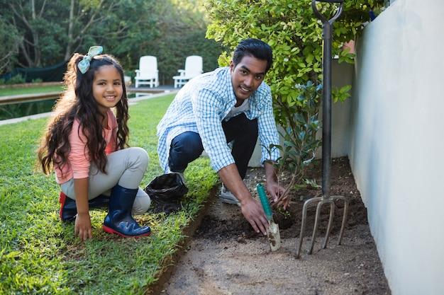 Отец и дочь, посадить дерево в саду на заднем дворе