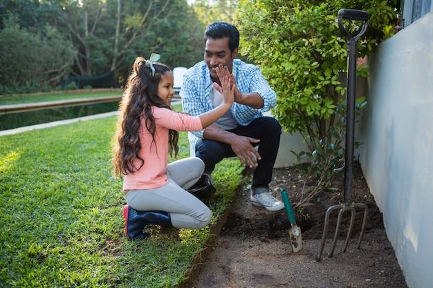 父と娘の裏庭の庭に木を植える