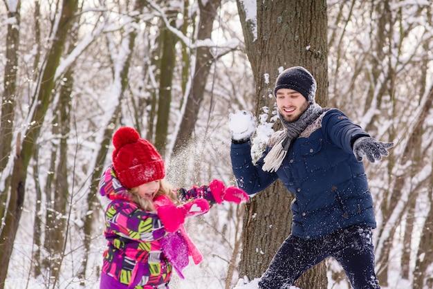 Отец и дочь играют в снежки в зимнем лесу