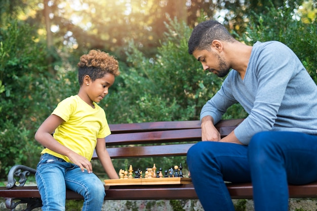Отец и дочь играют в шахматы в парке