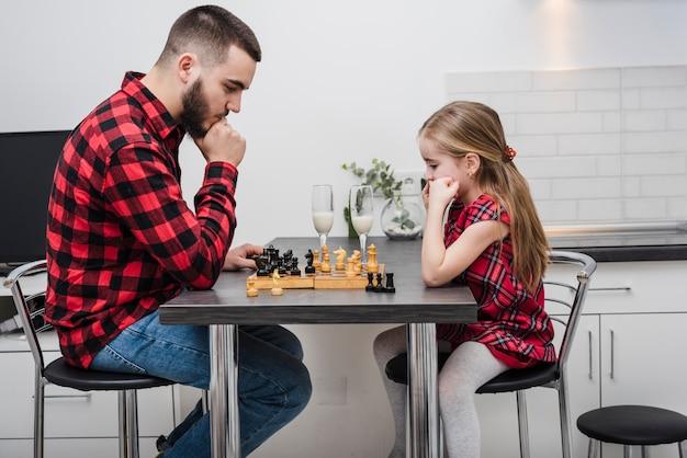 Отец и дочь играют в шахматы в день отцов